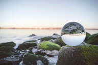 Close-up of a crystal ball on a rock at a beach in Southern France - INGF00446
