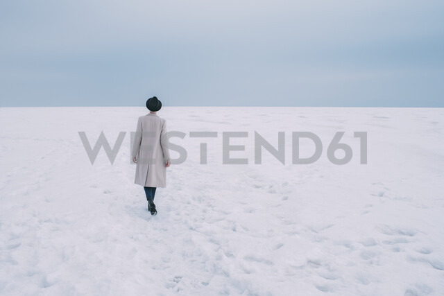 Woman in coat and hat walking in snow covered landscape - FSIF03178 - Vasily Pindyurin/Westend61