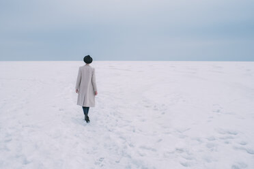 Woman in coat and hat walking in snow covered landscape - FSIF03178