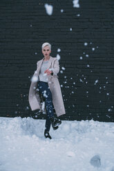 Portrait young woman kicking snow - FSIF03181