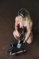 Athletic woman with dumbbells and earphones looking at cell phone - FMGF00038