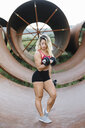 Athletic woman doing weight workout at industrial site - FMGF00044
