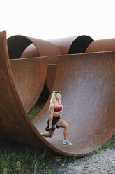Athletic woman doing weight workout at industrial site - FMGF00047