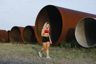 Athletic woman with cell phone and earphones walking at industrial site - FMGF00056