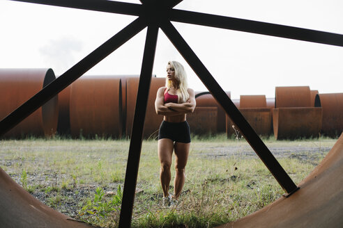 Confident athletic woman standing at industrial site - FMGF00062