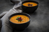 Bowl of carrot ginger coconut soup with topping of parsley and pomegranate seed - LVF07455