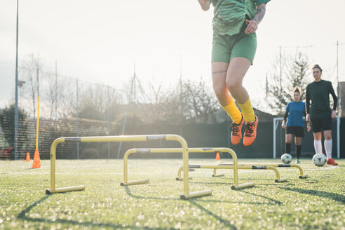 Football player jumping over hurdles - CUF45246