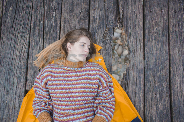Serious young woman lying on boardwalk looking away - AFVF01629 - VITTA GALLERY/Westend61