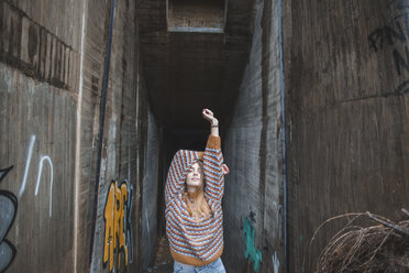 Portrait of young woman raising her arms at graffiti underpass - AFVF01632