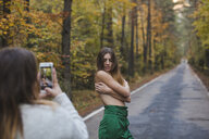 Woman taking cell phone picture of barechested young woman standing on country road - AFVF01641