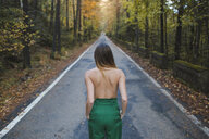 Rear view of shirtless young woman standing on country road - AFVF01644