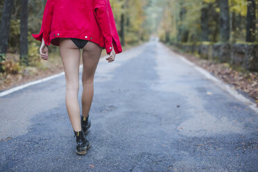 Young woman walking on country road wearing underpants and red jacket - AFVF01647