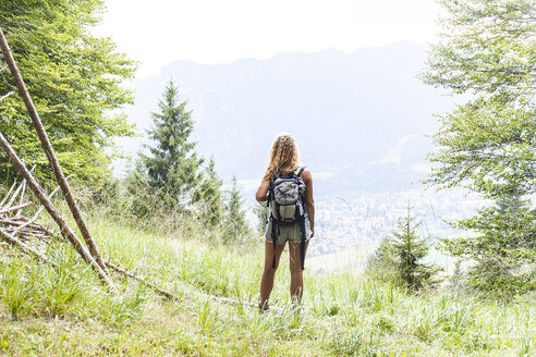 Germany, Bavaria, Oberammergau, young woman hiking standing on mountain meadow - TCF05828