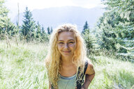 Germany, Bavaria, Oberammergau, portrait of smiling young woman hiking on mountain meadow - TCF05831