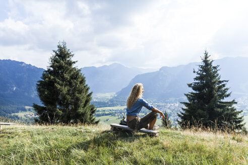 Germany, Bavaria, Oberammergau, young woman hiking sitting on bench on mountain meadow - TCF05837
