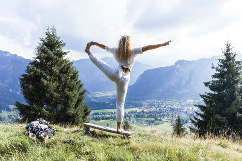 Germany, Bavaria, Oberammergau, young woman doing yoga on bench on mountain meadow - TCF05846