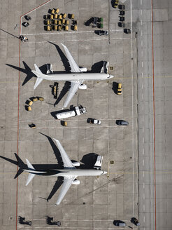 Aerial view commercial airplanes being serviced on tarmac at airport - FSIF03192