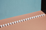 Sugar cubes in a row on peach background - FSIF03201