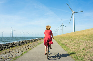 Girl cycling between onshore and offshore wind farm, Urk, Flevoland, Netherlands - CUF45377