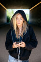 Young woman listening to music on mobile phone in tunnel - CUF45647