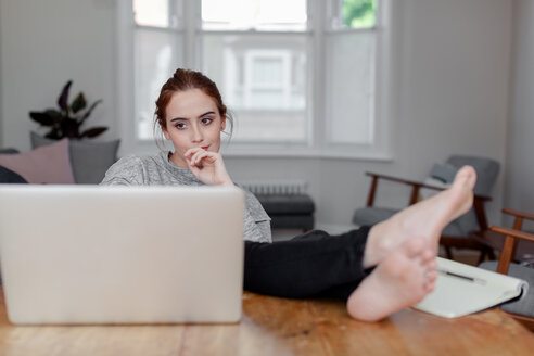 Woman using laptop on dining table - CUF45683
