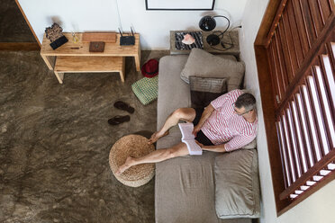 Mature man on sofa reading book, overhead view - CUF45743