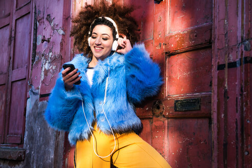 Portrait of woman with afro hair wearing fur coat, listening to music through headphones on smartphone - CUF45785
