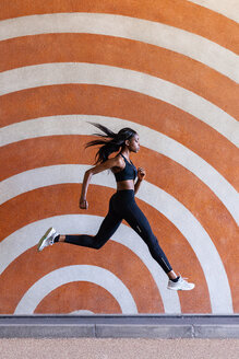 Young woman jumping against patterned background - CUF45800
