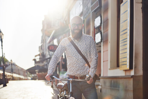 Portrait of bearded man with bicycle smiling at camera - CUF45926