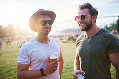 Two young male friends with glasses of beer at Holi Festival - CUF45953
