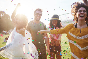 Young adult friends throwing and dancing in confetti at Holi Festival - CUF45956