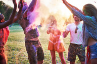 Five young adult friends dancing and throwing coloured chalk powder at Holi Festival - CUF45962