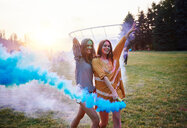 Two young women dancing with blue smoke bombs at Holi Festival - CUF45971