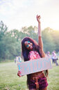 Young woman dancing while holding freedom sign at Holi Festival, portrait - CUF45974