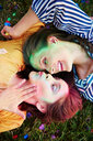 Two young women covered in coloured chalk powder lying on grass at Holi Festival, overhead view - CUF45977