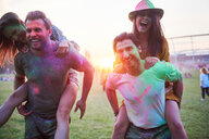 Two young couples covered in coloured chalk powder piggybacking at Holi Festival - CUF45983