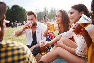 Friends sitting and enjoying music festival - CUF46022
