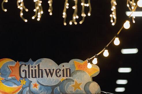 Germany, mulled wine sign at Christmas market by night - MMAF00617