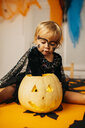 Portrait of little girl with painted face and fancy dress sitting on table playing with Jack O'Lantern - JRFF01879