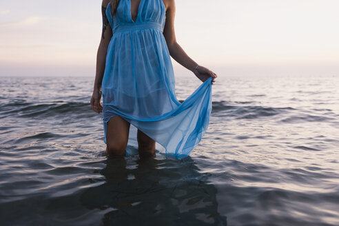 Young tattooed woman wearing blue dress standing in the sea by sunset, partial view - MAUF01721