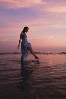 Young woman with tattoo standing in front of the sea by sunset - MAUF01727