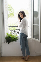Portrait of attractive young woman standing at the window - AFVF01656