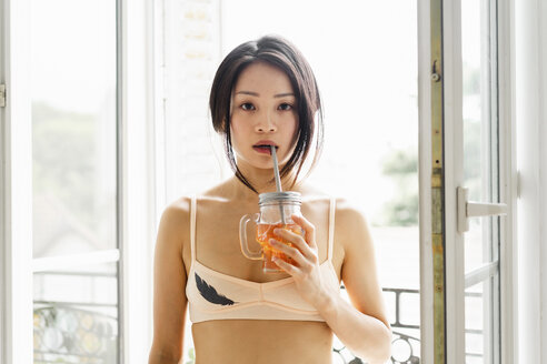 Portrait of attractive young woman wearing bra having a drink at the window - AFVF01674