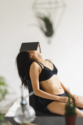 Young woman in lingerie sitting on chair at home covering her head with book - AFVF01677