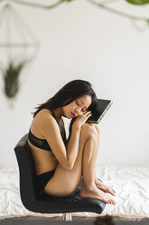 Attractive young woman in lingerie sitting on chair at home with book - AFVF01683