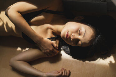 Attractive young woman in lingerie lying on the floor in sunlight - AFVF01686