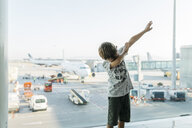 Spain, Barcelona airport, Boy in departure area, pretending to fly - JRFF01907