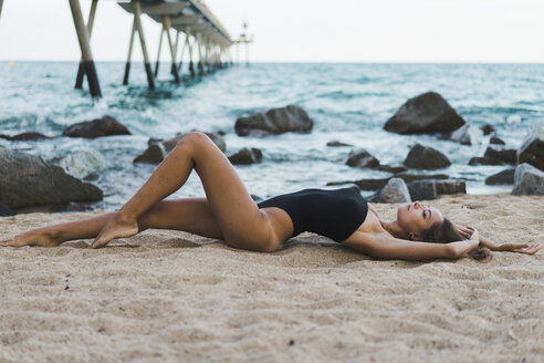 Beautiful young woman wearing swimsuit lying on the beach - AFVF01741