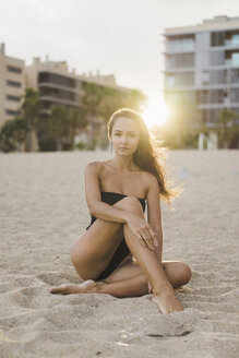 Portrait of beautiful young woman sitting on the beach at sunset - AFVF01747