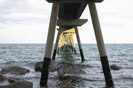 Sunlight shining on pier leading into the sea - AFVF01750